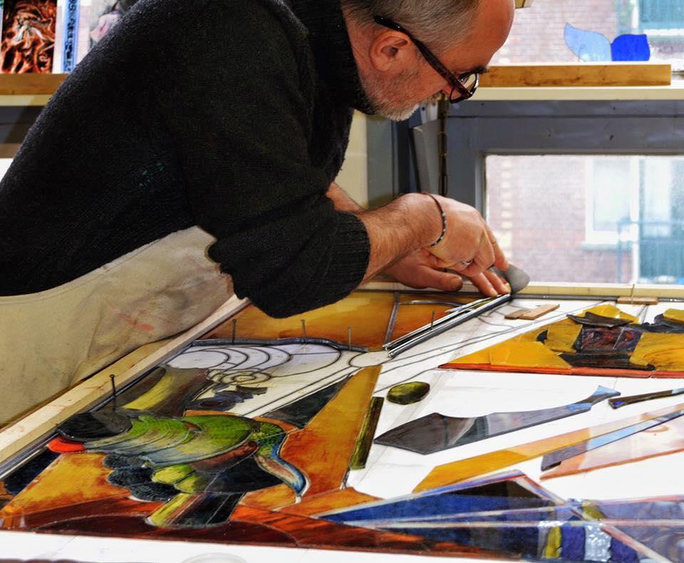 cursist aan het werk aan een glas in lood raam met gebrandschilderde stukken glas